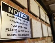 "Sign the says: ""NOTICE: PLAYING THE CARILLON REQUIRES INTENSE CONCENTRATION PLEASE DO NOT SPEAK DURING THE CONCERT"""