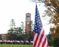 American flags lining the sidewalk by the campanile